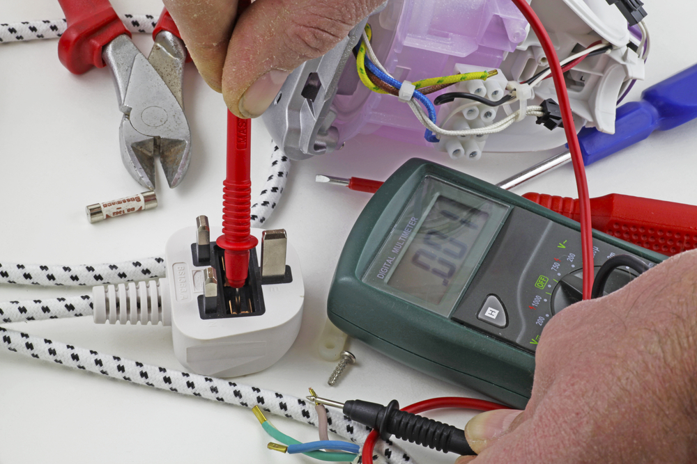 an electrician testing for a fault on the live cable with a multimeter